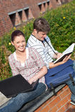 Couple of students working with book and laptop Stock Images