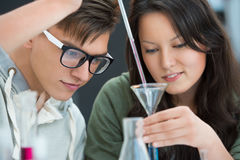 Couple of students working at chemistry classroom Stock Photos