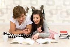 Couple studying. Teen couple lying on floor and doing homework Stock Photography