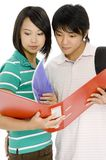 Couple Studying. A young asian couple looking at notes in a ring binder on white background royalty free stock photography