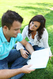 Couple Studying on Grass Royalty Free Stock Image