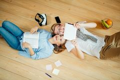 Couple studying while lying on floor at home Royalty Free Stock Photos