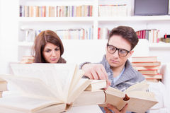 Couple studying together at home with lot of books Stock Image