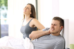 Couple suffering ache in a not comfortable bed. Couple waking up suffering ache after a bad night in a not comfortable bed at home or hotel room stock photo