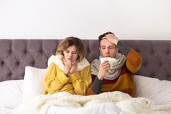 Couple suffering from cold in bed. Couple suffering from cold together in bed Stock Image