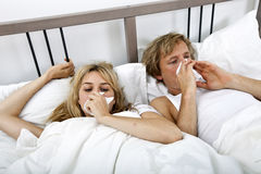 Couple suffering from cold lying on bed Royalty Free Stock Images