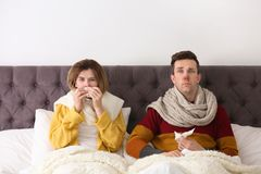 Couple suffering from cold in bed. Couple suffering from cold together in bed Royalty Free Stock Photos