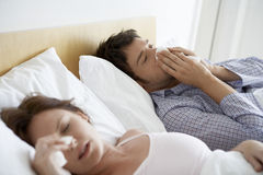 Couple Suffering From Colds In Bed. Young couple suffering from colds in bed Stock Images