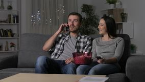 Couple suffering power outage claiming on phone. Couple suffering power outage while watch tv claiming on phone and solving problem in the night at home stock footage
