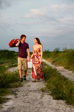 Couple with suitcase. Couple walking together, holding hands and carrying a suitcase Stock Photo