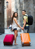 Couple with suitcases. Happy couple with suitcases walking in the street summer day Stock Image