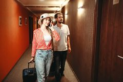 Couple with suitcases looking for their hotel room. Happy couple with suitcases looking for their hotel room. Travelling or tourism concept, summer vacation royalty free stock photos