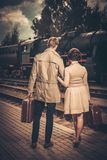 Couple with suitcases on a train station. Vintage style couple with suitcases on train station platform Royalty Free Stock Images