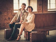 Couple with suitcases on a train station. Vintage style young couple with suitcases on a train station Stock Image