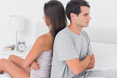 Couple sulking each other sitting back to back on bed royalty free stock images
