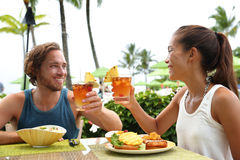 Couple on summer vacation toasting mai tai drinks. Happy multiracial couple toasting cheers with alcoholic hawaiian drink, Mai Tai, Hawaii experience. Summer royalty free stock images