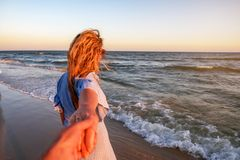 Couple summer vacation travel - Woman walking on romantic honeymoon beach holidays holding hand of boyfriend following her. View from behind. POV stock images