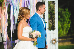 Couple in Sun. Bride and groom standing at decorated gate in sun Royalty Free Stock Image