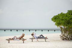 Couple on the sun loungers. The couple lie on the sun loungers on the beach stock images