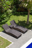 Couple of sun loungers beside the pool in tropical garden.  Bali, Indonesia Royalty Free Stock Photography