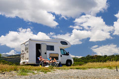 Couple is sunbathing. In front of a motor home royalty free stock photo