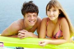 Couple sunbathing. Portrait of teenage girl in bikini and her boyfriend lying on mattress and sunbathing Royalty Free Stock Photo