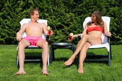 Couple sunbathing in back yard and drinking cocktails Royalty Free Stock Images