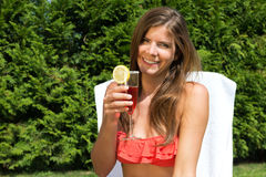 Couple sunbathing in back yard and drinking cocktails Stock Photo