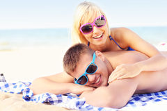Couple sunbathing at the beach Stock Images