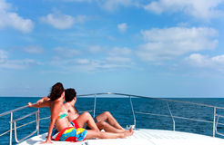 Couple Sunbathing On The Bow Of The Boat. Lifestyles. Man and woman sunbathing on the bow of a motor boat in the sea Royalty Free Stock Photo