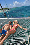 Couple sunbathing on catamaran in caribbean sea Stock Photo