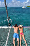 Couple sunbathing on a catamaran in caribbean sea Royalty Free Stock Photos