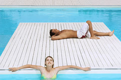 Couple Sunbathing At Poolside. Young men and teenage girl sunbathing at poolside Stock Photography