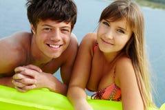 Couple sunbathing. Portrait of teenage girl in bikini and her boyfriend lying on mattress and sunbathing Royalty Free Stock Images