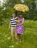 Couple with sunflower and yellow umbrella Stock Photos