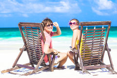 Couple in sunglasses on sun lounger on tropical Stock Photos