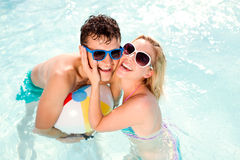 Couple with sunglasses in swimming pool. Summer, sun, water. Man and women in bikini and sunglasses in the swimming pool, with baloon. Summer heat, sun and Stock Photos