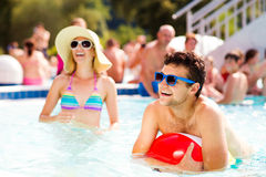 Couple with sunglasses in swimming pool. Summer and water. Man and women in bikini with sunglasses in the swimming pool, with baloon. Summer heat and water Royalty Free Stock Photography