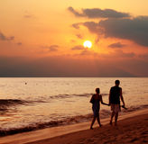 Couple at sunset. Couple walking on the beach at sunset Royalty Free Stock Image