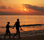 Couple at sunset. Couple walking on the beach at sunset with some motion blur Stock Image