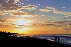 Couple on sunset beach walk. Silhouette of couple holding hands on sunset beach walk Stock Photos