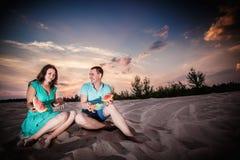 Couple, sunset, evening, beach, sitting Royalty Free Stock Photos