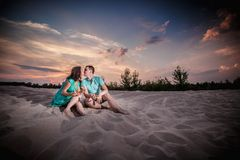Couple, sunset, evening, beach, sitting Royalty Free Stock Photo