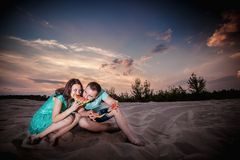 Couple, sunset, evening, beach, sitting Stock Photos