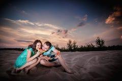 Couple, sunset, evening, beach, sitting Stock Photos