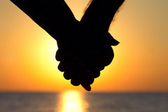 Couple at sunset holding hands royalty free stock images