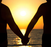 Couple at sunset holding hands stock photo
