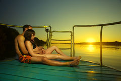 Couple in sunset hug on boat Royalty Free Stock Image