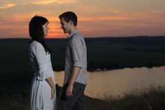 Couple at sunset and lake. Couple sweethearts at sunset and lake Royalty Free Stock Image