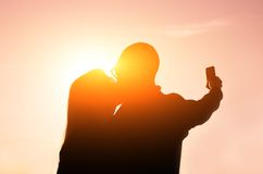 Couple at sunset taking a selfie. Couple kissing themself at sunset while taking a selfie with phone Royalty Free Stock Photo